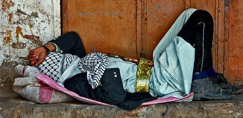 Un uomo riposa lungo una via di Shibam